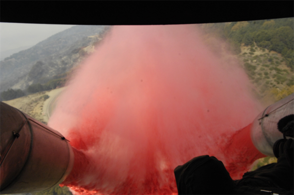 Approximately 3,000 gallons of fire retardant is deployed Oct. 25 over the Poomacha fire in North San Diego County, Calif. The C-130 Hercules and crew are assigned to the 302nd Airlift Wing from Peterson Air Force Base, Colo. The aircraft launched from Channel Islands Air National Guard Station, Calif. (U.S. Air Force photo/Tech. Sgt. Roy A. Santana)