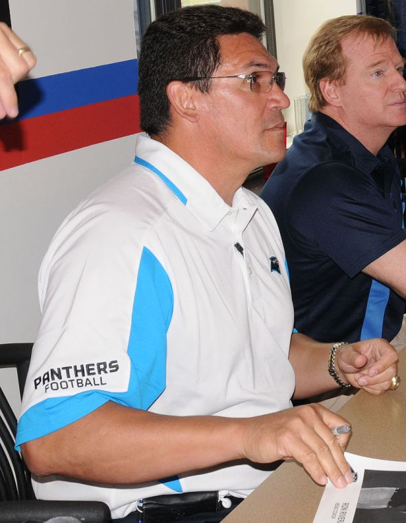 Photo Credit: Reginald RogersParaglide Carolina Panther head coach Ron Rivera, left, NFL Commissioner Roger Goodell and former Carolina Panthers player Mike Rucker sign autographs and photos for Soldiers at the 1st Brigade Combat Team dining facility Friday during their visit to the post.