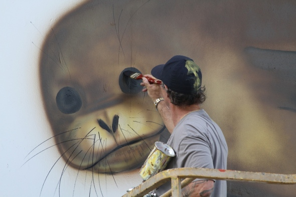 The artist Wyland, who goes by only one name, paints a mural on Charlie Barracks, a former military barracks still in use on Midway. Midway Atoll National Wildlife Refuge, Papahānaumokuākea Marine National Monument January 2012 Photo: Pete Leary/USFWS